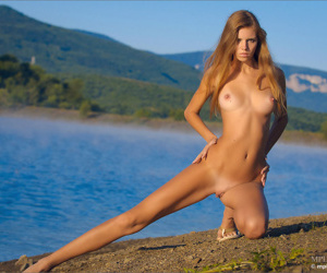 Perky titted blonde poses naked at the lake showing high perky breasts
