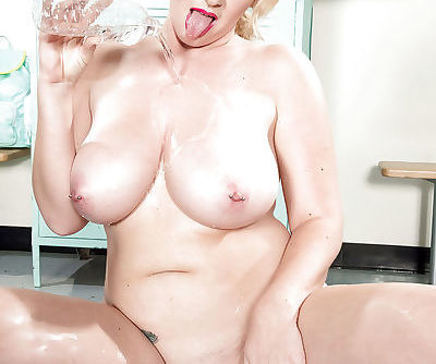 Chunky blonde mom Rockell pouring water over pierced nipples on yoga mat