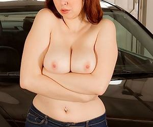 Bosomy redhead chick with ample booty slowly getting rid of her clothes
