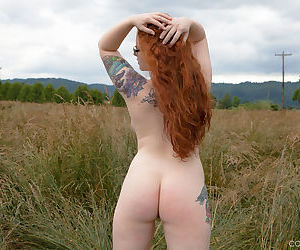 Hot redhead BBW Kaycee looses her huge tits and gets on her knees in a field