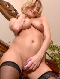Sexy older woman Lya Pink slips off black dress before masturbating in nylons