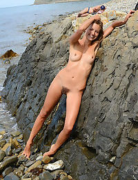 Slender brunette Geissa poses nude on the rocks showing her hairy beaver