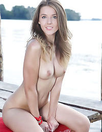 Slim brunette Sybil A baring small perky tits & bald pussy close up on wharf
