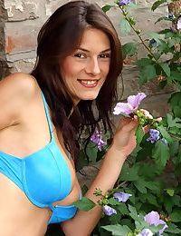 Brunette teen unveils her nice tits before masturbating in the garden