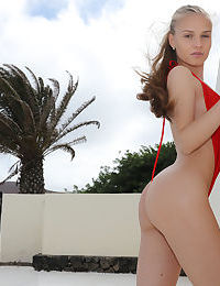 Young solo girl Angel B removes her V shaped swimsuit to model in the nude
