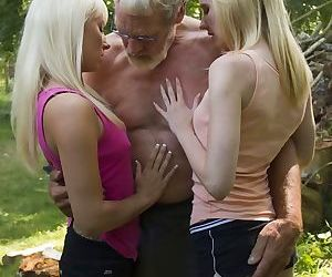 Young blonde girls give an old man a double blowjob during a threesome
