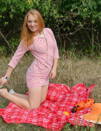 Young girl with red hair holds an orange while posing naked on a blanket