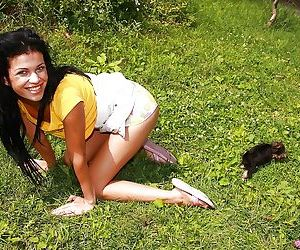 Young busty babe is playing with big dildo on a green grass field