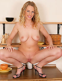 Curly-haired blondie undressing and playing with herself in the kitchen