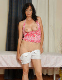 Mature brunette Renie doffs her shorts and gets busy with toying her pussy