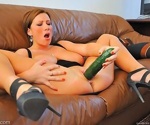 Leggy model changes dressed prior to pleasing herself with a cucumber