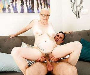 Horny granny with tattoos has her toy boy fill her pussy with jizz
