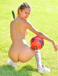 Skinny young girl posing naked in socks outdoors in public park