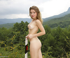 Young solo girl Malinda A climbs a mountain to pose in the nude