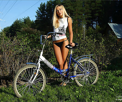 Blonde girl with long legs and a tight ass rides her bicycle in the nude
