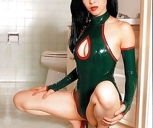 Playful asian babe slipping off her sexy latex outfit in the bathroom