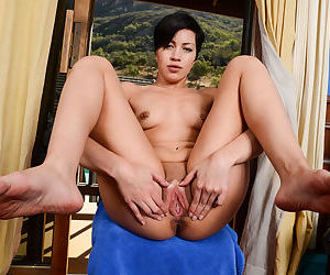 Brunette solo model Jade Rox plays with her hairless vagina after disrobing