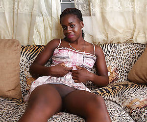 Black amateur Kima undressing on couch before displaying pink vagina