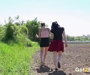 Young girls crossing a freshly planted field take a pause for a pee