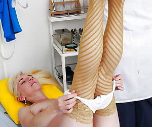 Stocking clad mature woman inserting speculum into hairy vagina