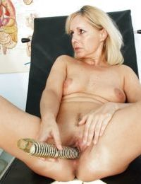 Mature blonde with puffy nipples toying her twat in gyno room