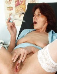 Naughty mature lady toying her bushy twat in the gyno office