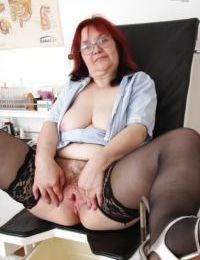 Fatty redhead mature nurse in glasses toying her twat in gyno office
