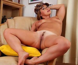 Middle-aged female proudly shows off her shaved vagina after undressing