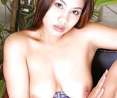 Dark-haired Asian model with big boobies is posing and playing