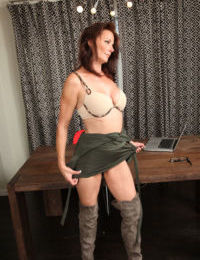 Older woman Mimi Moore flashes a no panty upskirt prior to disrobing on a desk