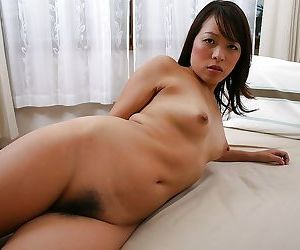 Fuckable asian MILF posing unveil with the addition of showcasing her queasy gash in counter
