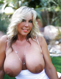 Big boobed blond housewife Sandra Otterson posing topless outdoors in heels