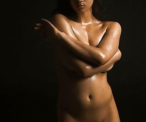Naked Indian female exposes a single breast while modeling in the dark