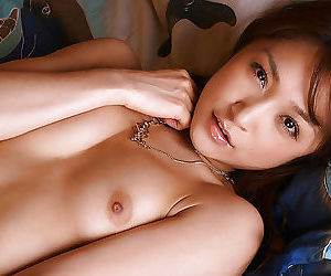 Loveable asian cutie in stockings and lingerie stripping on the bed