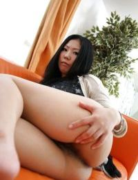 Sassy eastern MILF undressing and stretching her hirsute twat in close up