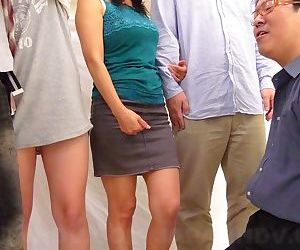Grown up Japanese skirt fingers her hairy pussy in unusual gloryhole style orgy