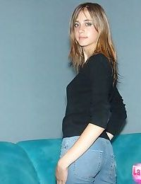 Amateur solo girl in bare feet and jeans starts to remove her sweater