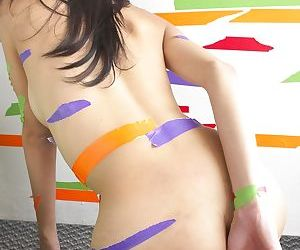 Colorful tape covers slender transsexual body during her play with dildo