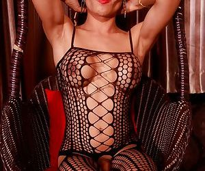 Ladyboy in a revealing bodystocking drips jizz from her uncut cock