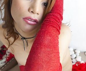 Redhead babe Anny exposes her small dick in hot fishnet stockings