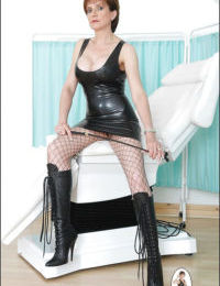 Stunning mature woman posing in latex dress and fishnet pantyhose