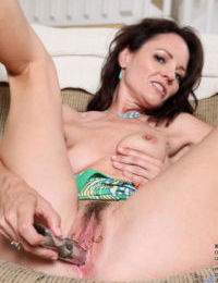 Mature brunette Danielle Reage toys her trimmed muff in pointy high heels