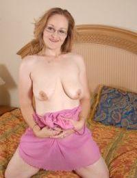 Mature Venus is sucking her pretty hard nipples in the bedroom