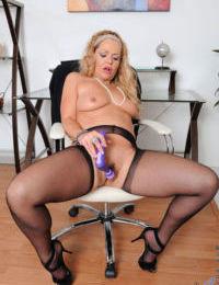 Mature businesswoman Kelly Leigh masturbates behind inside her office