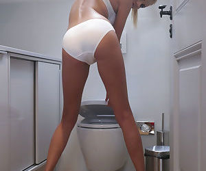 Young blonde Odara D poses for a glam shoot in heels on toilet while smoking