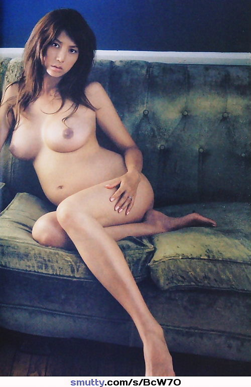 Sexy pregnant Asian on a couch