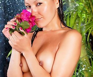 Young Asian wet with the tropical plants and nude for sexy pics