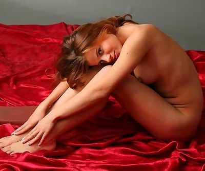 Aida B lies on the soft red sheet and shows how flexible she can be
