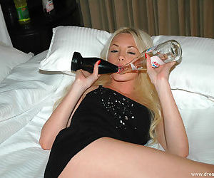Teen blonde in a little black dress is licking bottles and showing cleavage