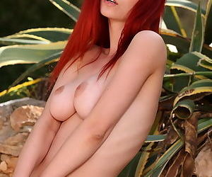 Redhead outdoors in erotic nude set where we see her trimmed pussy